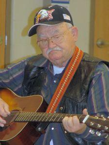 retired man playing guitar