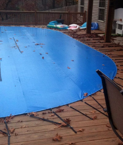 winter cover strapped to pool deck
